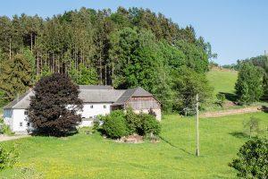 Der Dreikanthof HÖF15 umgeben von Wiesen, Wald & Wasser mit der Burgruine Waxenberg im Hintergrund.